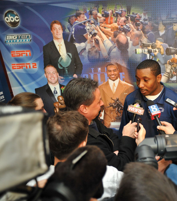 Members of the media interviewing a football player.