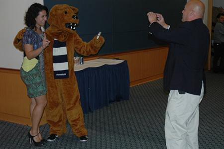 Assistant Dean Jamey Perry snaps a picture of Marielena Balouris with the Nittany Lion.