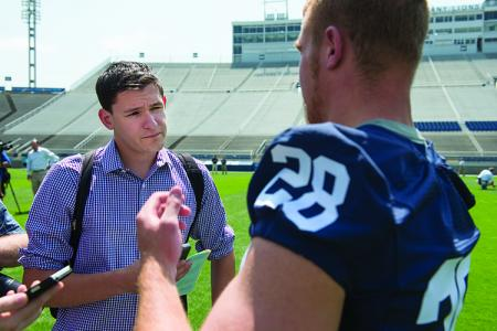 Gilbert listens to running back Zach Zwinak during a one-on-one intervew. (Photo by Curt Chandler)