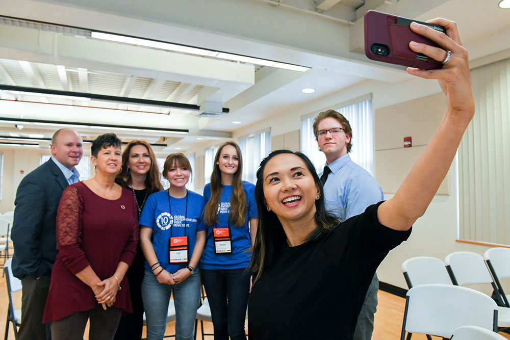 Guest speaker photographs a selfie with College students behind her