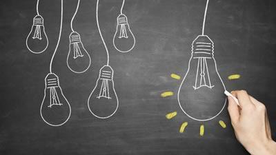 Chalk-drawn lightbulbs on a chalk board