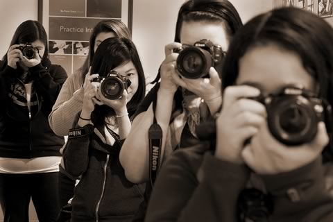Five students with camera lenses pointing at the photographer