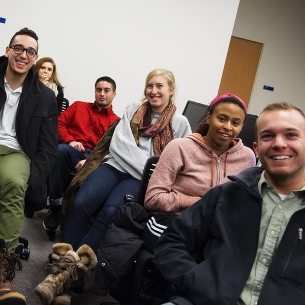 A group of students in class relax and pose for the camera