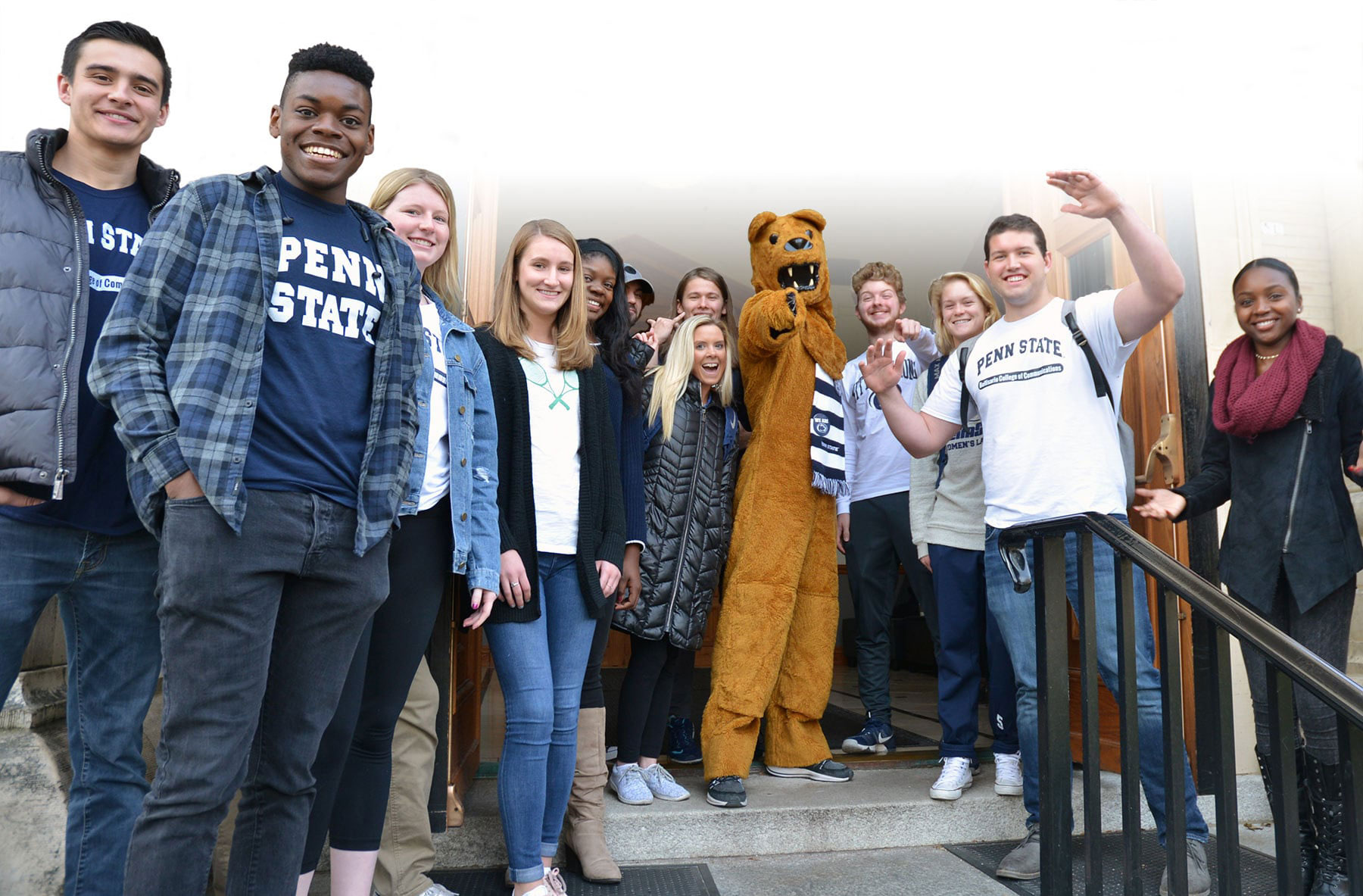 The Nittany Lion mascot points his finger at the camera while posing with a bunch of students on the Carnegie Building steps