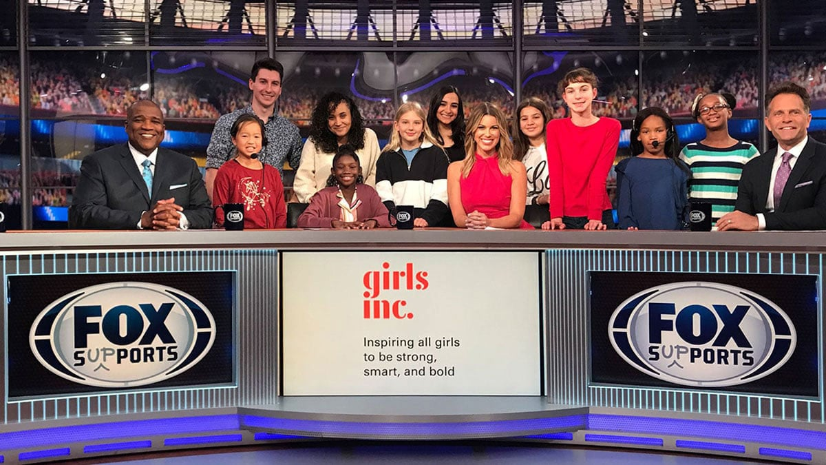 Penn State students and Alumni on set at Fox Sports with a bunch of young girls and a graphic that reads, Girls, Inc.: Inspiring all girls to be strong, smart, and bold