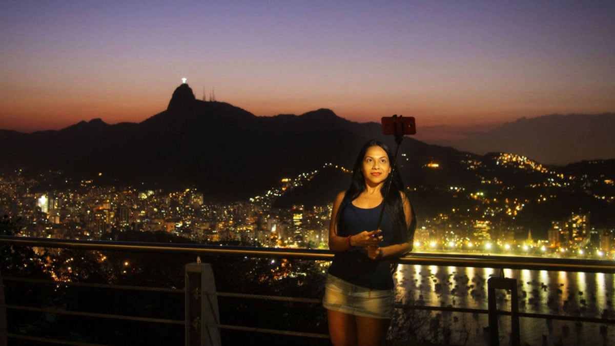 A Student captures a selfie as the sun sets in Rio with the cityscape behind