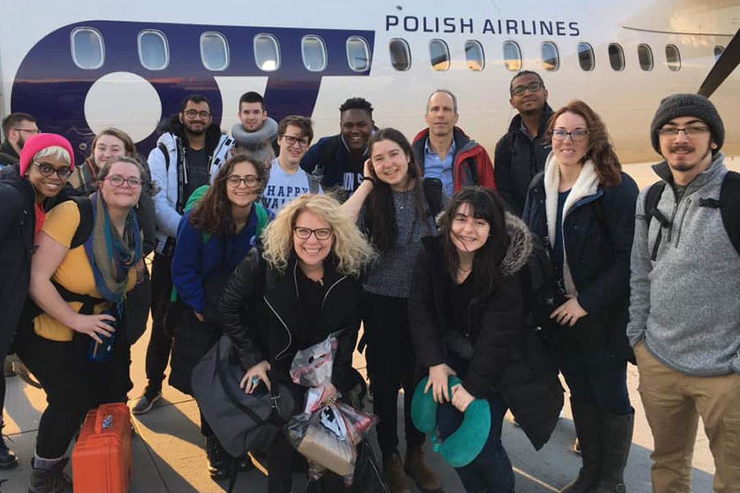A mixed group of faculty and students on an international course experience pose in front of a Polish Airlines jet.