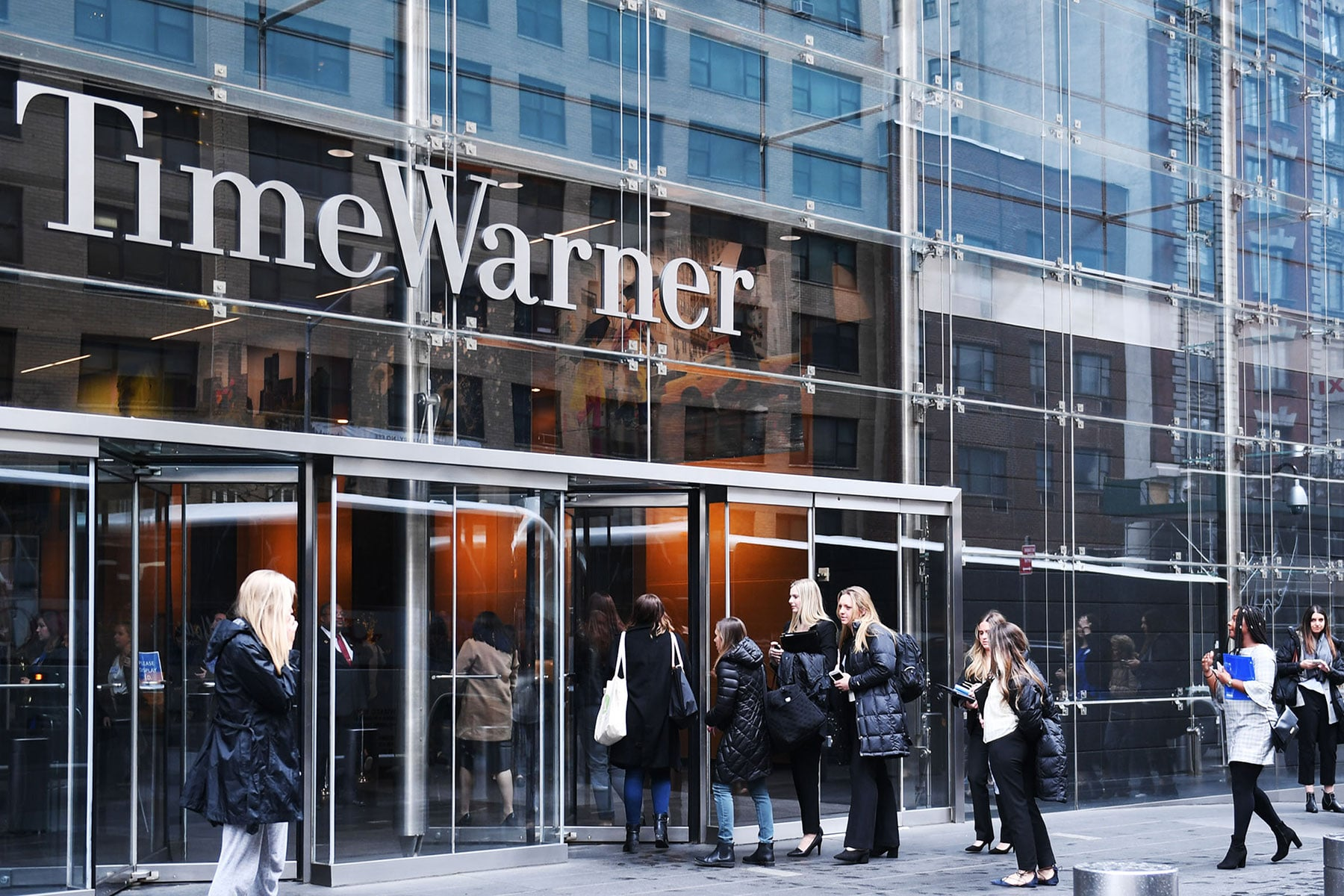 A number of young women dressed in winter clothes, file into an office building with the Time Warner logo above the door