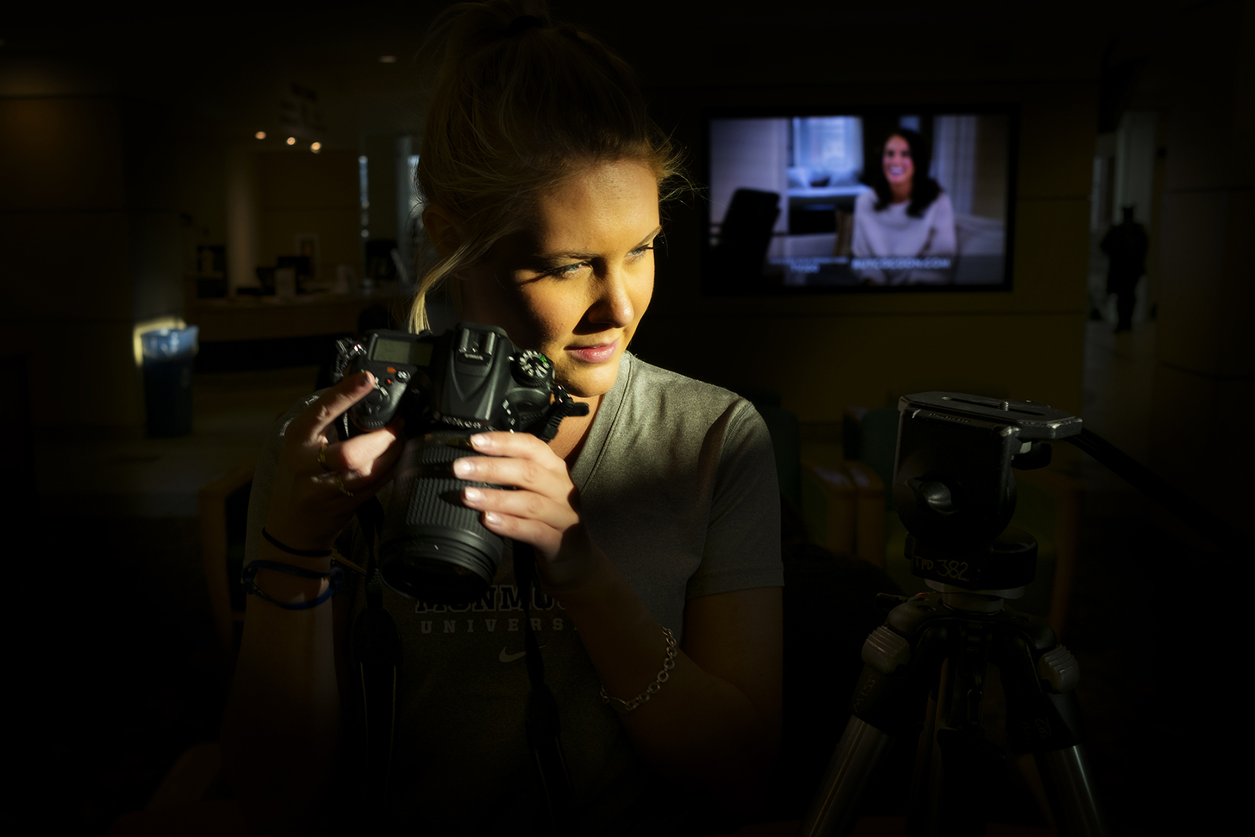 A young woman's face and camera are lit by stylish light with a very dark, moody background