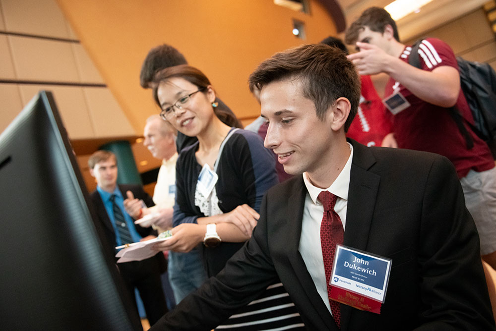 A student dressed in suit and tie demos a project on his computer for a faculty reviewer.