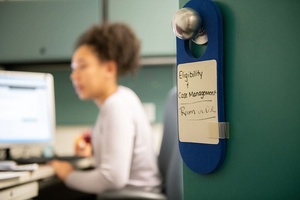 Super soft focus background of a woman on a laptop. In the foreground in focus is a door hangar that reads - Eligibility and Case Management - Room in Use