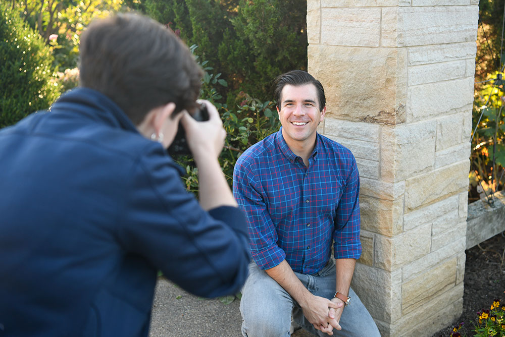 A CommAgency photographer shoots a head shot in front of a stone pillar on campus.