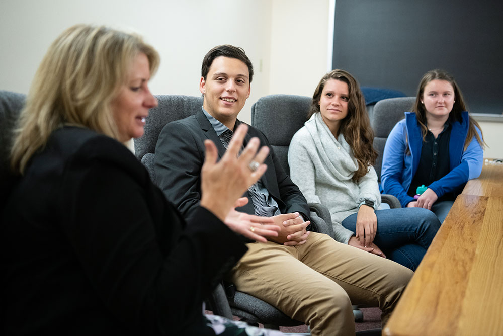 Soft focus photo of a blond woman talking to several students around a conference table.