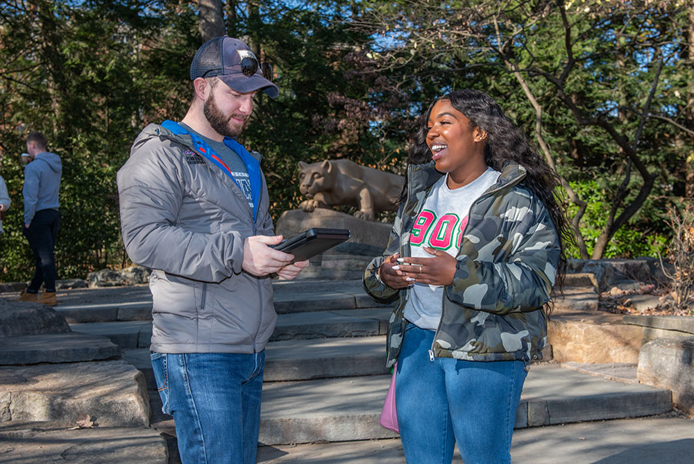 A student on a tablet running a survey asks questions of another student with the lion shrine in the background.