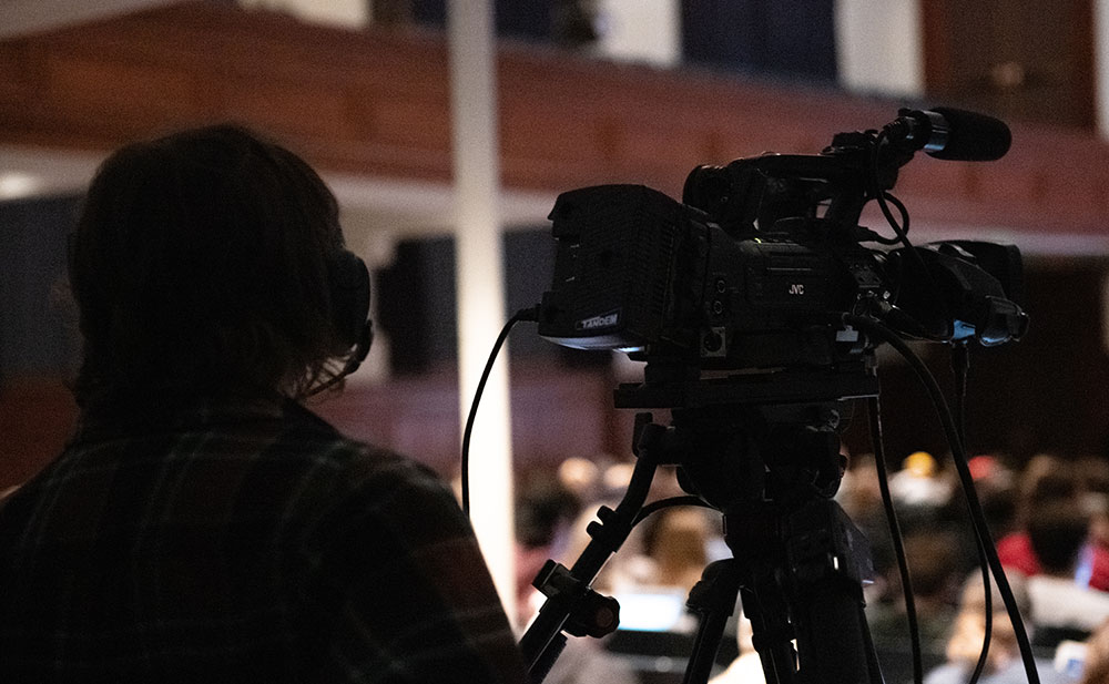 CommAgency camera operator filming a presentation for a live stream.