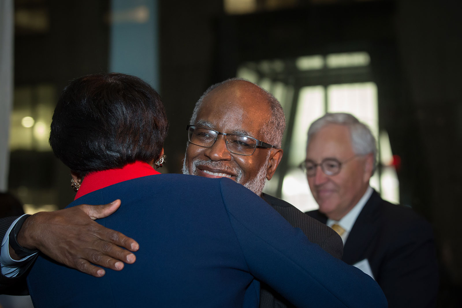 Lisa Davis and Bert Ifill embrace at the Page Center Awards, as past honoree Dick Martin looks on.